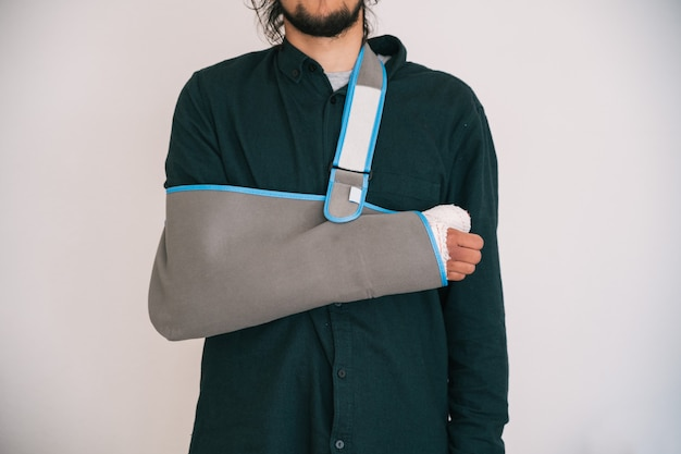 Young man with a bandaged arm and a textile sling holding his arm