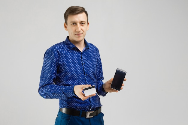 Young man with a bank card and mobile phone stands isolated