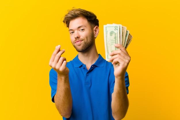 Молодой человек с банкнотами на оранжевом фоне