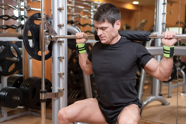 Young man with barbell doing squats in gym.
