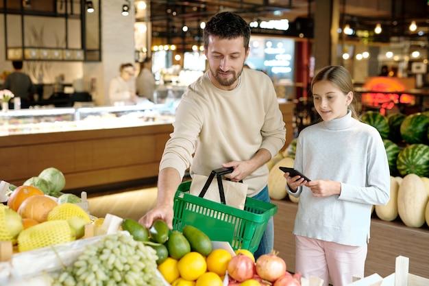 Молодой человек с корзиной и его дочь, выбирая авокадо