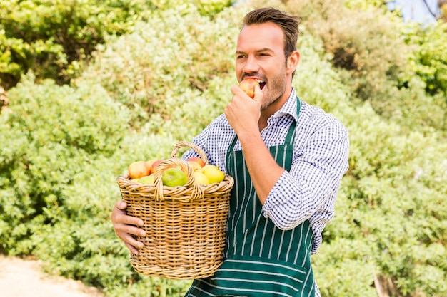 Young man with basket eating apple