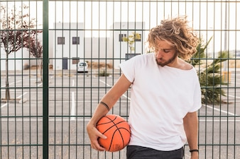Young man with basketball standing against fence
