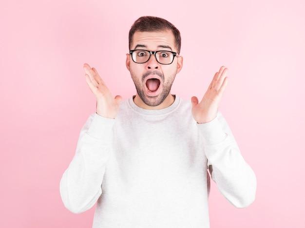 ピンクの背景の上にカジュアルなセーターを着ているひげと眼鏡の若い男