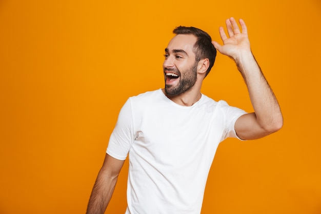 Молодой человек с бородой и усами улыбается и машет рукой, стоя, изолированный на желтом