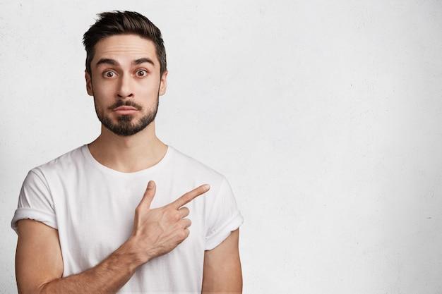 Молодой человек с бородой и белой футболкой