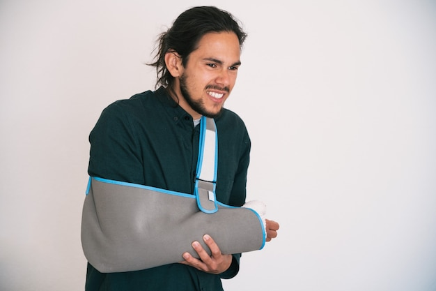Young man with beard a bandaged arm and a textile sling holding his arm with an expression of pain