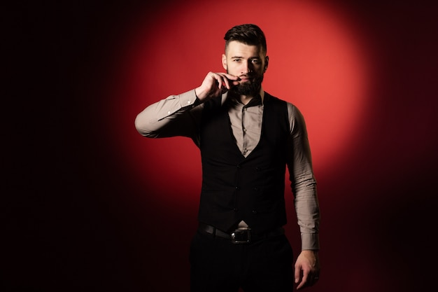 Young man with beard in black vest posing in studio with red background. a man straightens his mustache with his hand