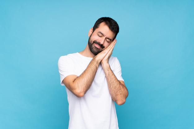 Young man with beard  over blue making sleep gesture in dorable expression