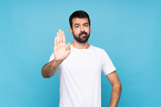 Young man with beard  over blue making stop gesture