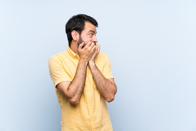 Young man with beard  on blue  nervous and scared putting hands to mouth