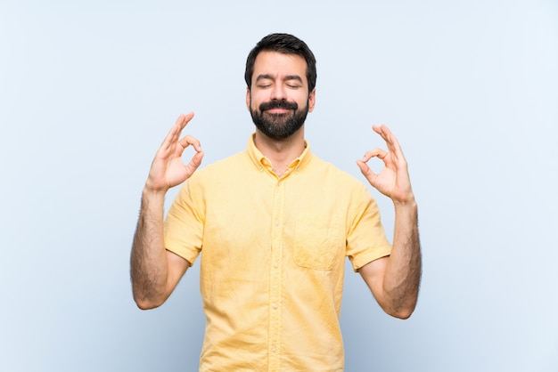 Young man with beard  on blue  in zen pose