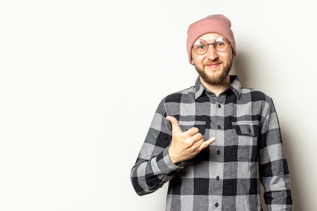 Young man with a beard in a hat, a checkered shirt makes a gesture of shaka on an isolated white. greeting gesture