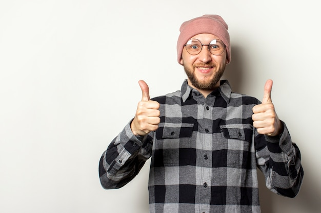 Young man with a beard in a hat, a checkered shirt makes a gesture thumb up on an isolated white. the gesture is all right, ok, verified