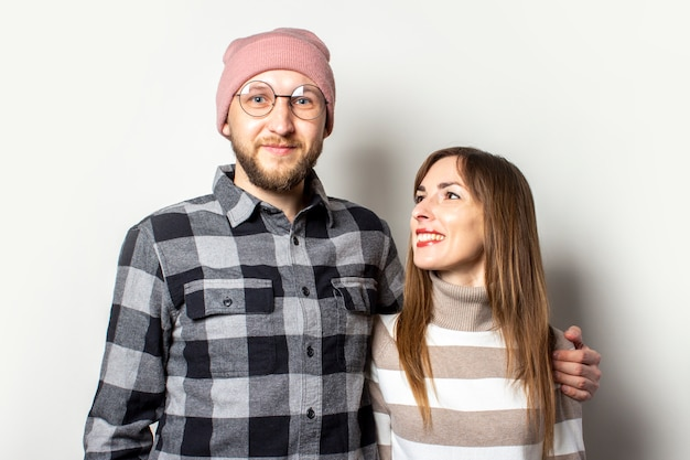 Young man with a beard in a hat and a plaid shirt hugs a girl in a sweater on an isolated light background.