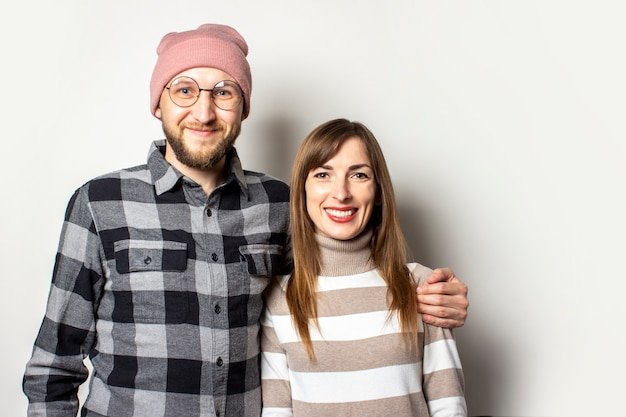 Young man with a beard in a hat and a plaid shirt hugs a girl in a sweater on an isolated light