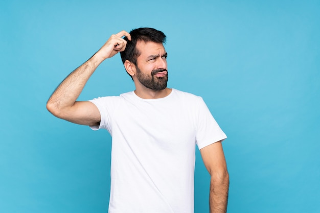 Young man with beard having doubts while scratching head