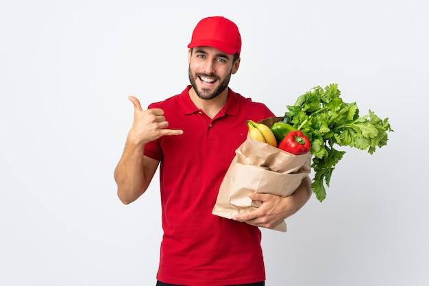 電話ジェスチャーを作る白い背景で隔離の野菜でいっぱいのバッグを保持しているひげを持つ若い男