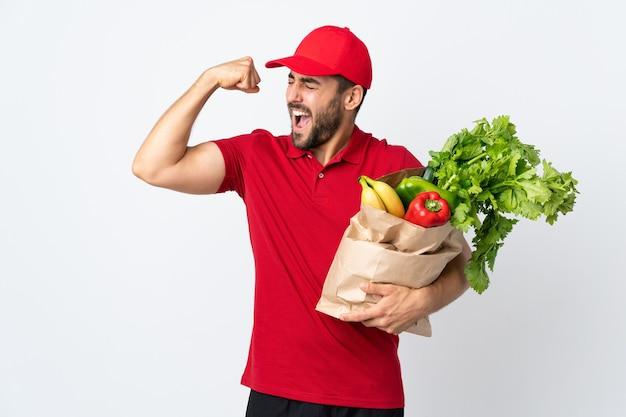 Молодой человек с бородой держит сумку, полную овощей, изолированную на белом, празднует победу