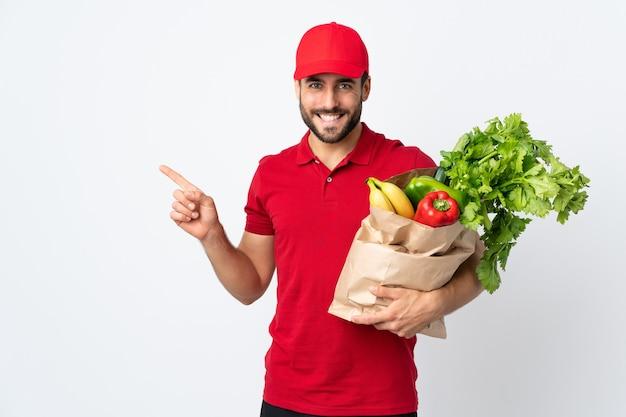 Молодой человек с бородой держит сумку, полную овощей, изолированную на белом, указывая пальцем в сторону