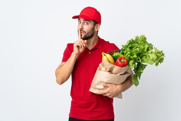 Молодой человек с бородой, держа сумку, полную овощей, изолированные на белой стене, делая жест молчания