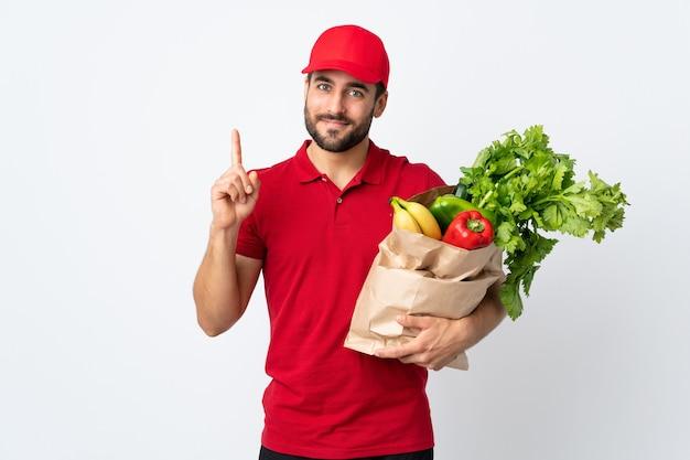 人差し指で指している白い壁に分離された野菜でいっぱいのバッグを保持しているひげを持つ若い男は素晴らしいアイデア