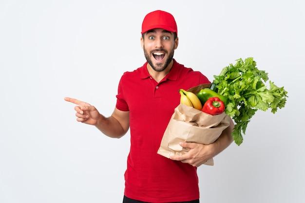 Молодой человек с бородой, держа мешок с овощами на белой стене, указывая пальцем в сторону
