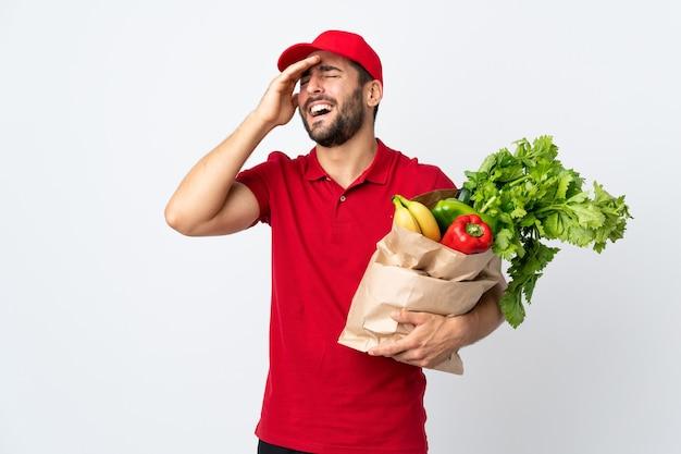 野菜がいっぱい入った袋を持っているひげを持つ若い男