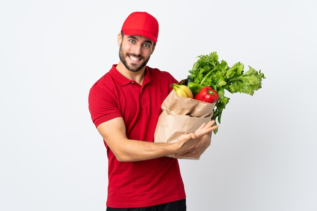 Young man with beard holding a bag full of vegetables isolated on white wall extending hands to the side for inviting to come