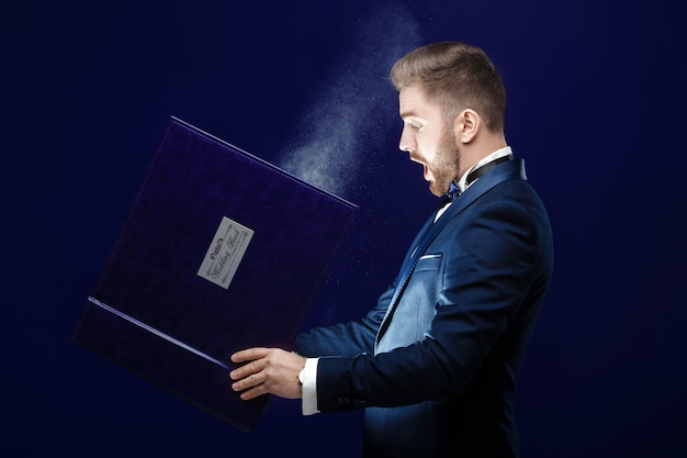 Young man with beard holding book with magic light
