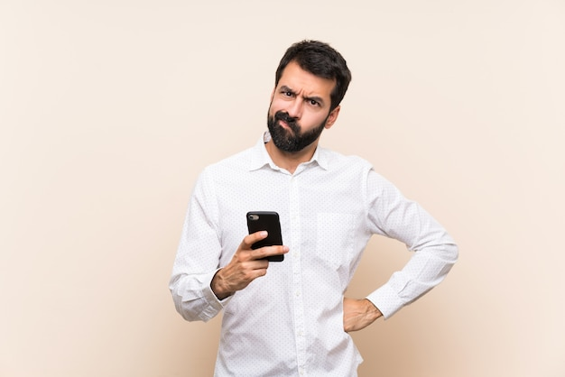 Young man with beard holding a mobile angry
