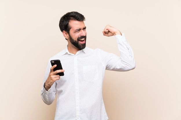 Young man with beard holding a mobile celebrating a victory
