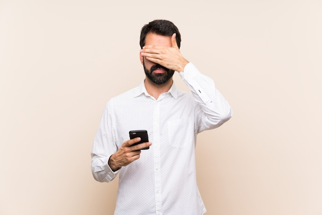 Young man with beard holding a mobile covering eyes by hands. do not want to see something