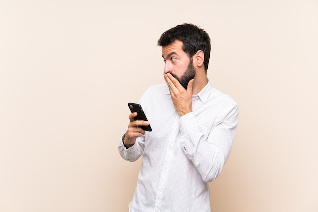 Young man with beard holding a mobile covering mouth and looking to the side