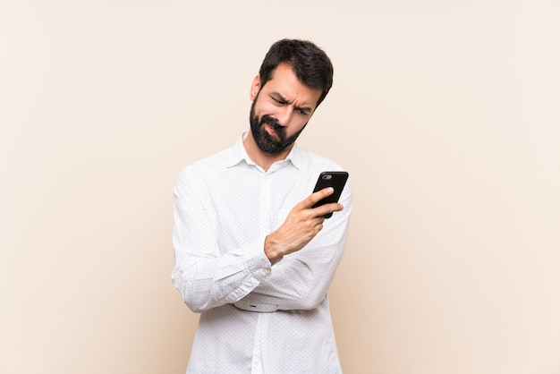 Young man with beard holding a mobile feeling upset