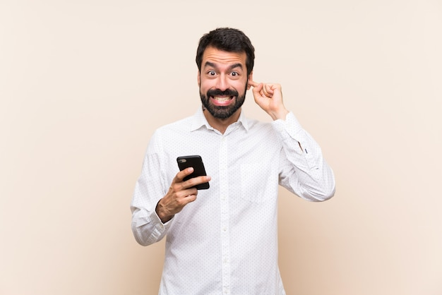Young man with beard holding a mobile frustrated and covering ears