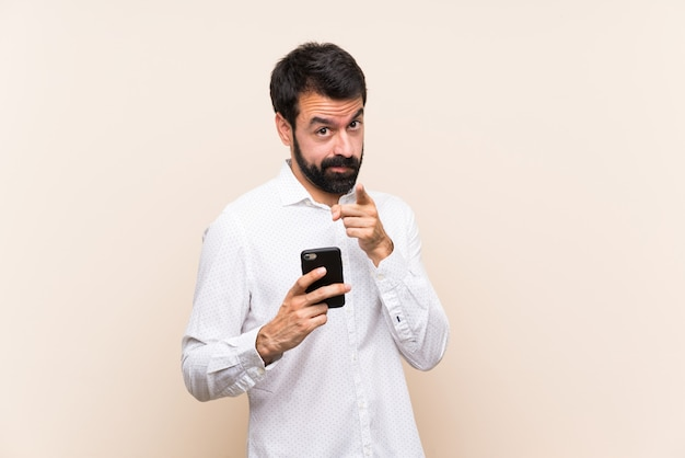 Young man with beard holding a mobile frustrated and pointing to the front