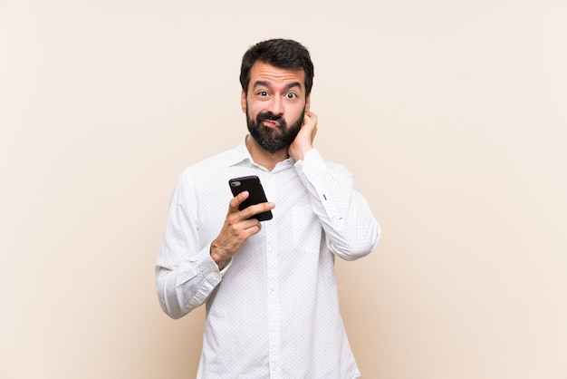 Young man with beard holding a mobile having doubts