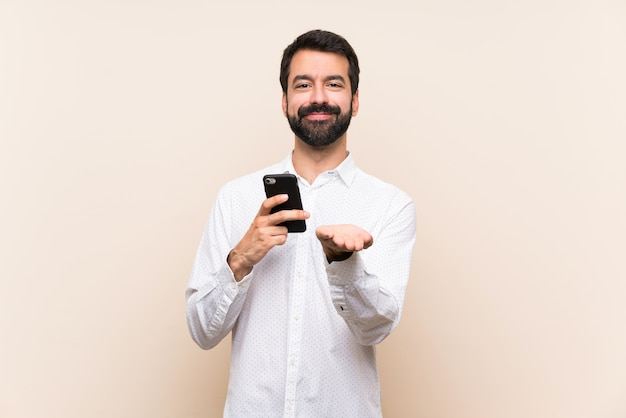 Young man with beard holding a mobile holding copyspace imaginary on the palm to insert an ad