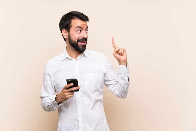 Young man with beard holding a mobile intending to realizes the solution while lifting a finger up