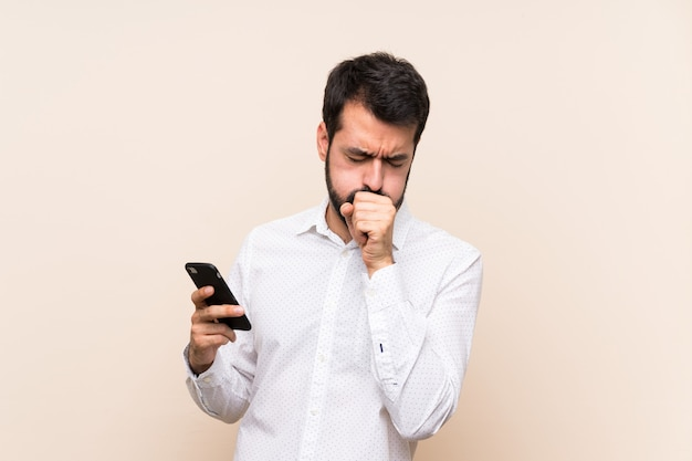 Young man with beard holding a mobile is suffering with cough and feeling bad