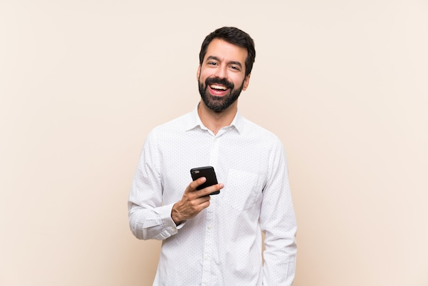 Young man with beard holding a mobile laughing