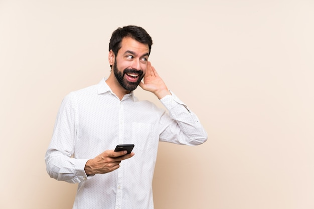 Young man with beard holding a mobile listening to something by putting hand on the ear