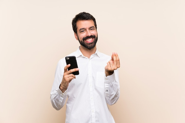Young man with beard holding a mobile making money gesture