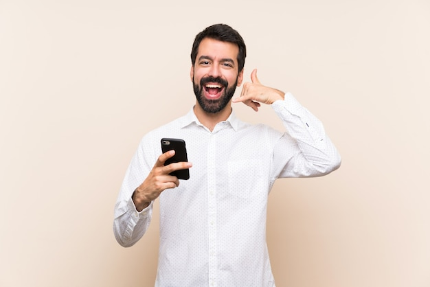 Young man with beard holding a mobile making phone gesture. call me back sign