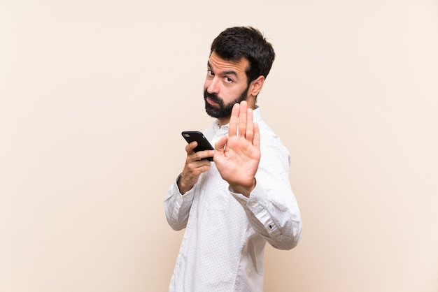 Young man with beard holding a mobile making stop gesture and disappointed
