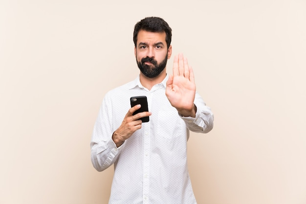 Young man with beard holding a mobile making stop gesture