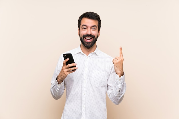Young man with beard holding a mobile pointing up a great idea