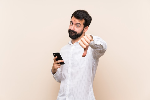 Young man with beard holding a mobile showing thumb down with negative expression