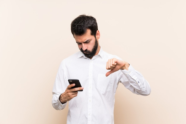 Young man with beard holding a mobile showing thumb down
